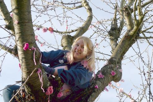 The author, Monica Miller, attaches yarn blossoms from the bow of the tree.