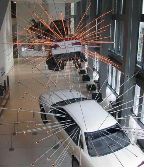 Automobiles exploding with light dangle from the ceiling at the Seattle Art Museum