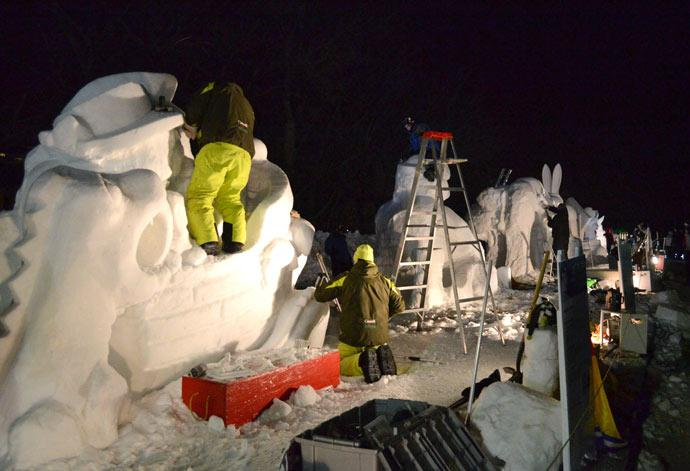 Watch artists from around the world create snow sculptures
