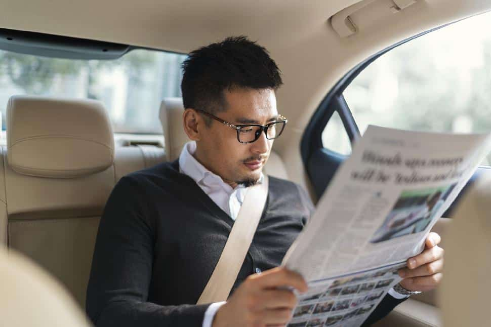 car uber man reading newspaper