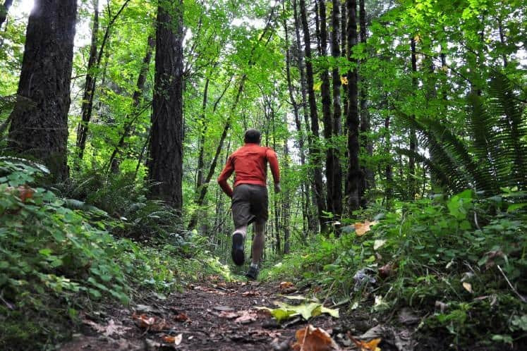 Man running through forest