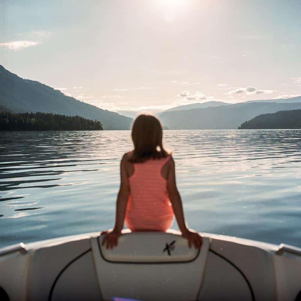 A girl on the bow of a boat enjoys the views over the lake