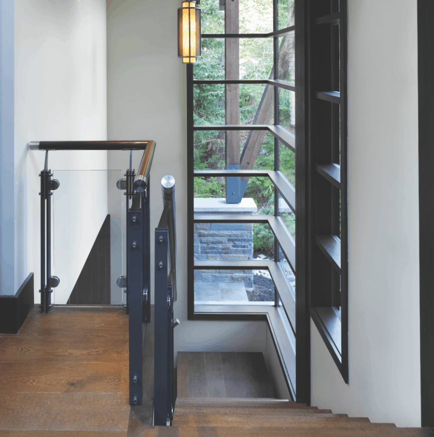 STAIRWAY: The stairs feature glass-and-steel rails that reiterate the steel trusses of the great room.