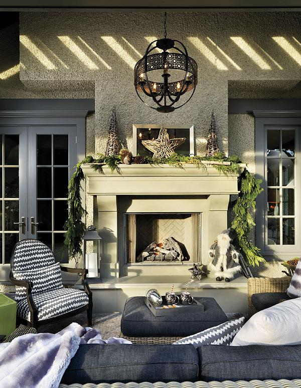 Bring holiday warmth outside with cozy throws and greens The outdoor room is still well used once the temperature drops, thanks to heaters and a fireplace. It's draped with live greens, faux-fur throws and rustic decorations like the stars and trees mad
