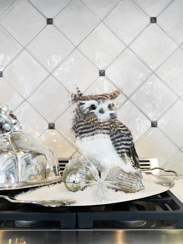 A sense of humour is always appreciated. The owl decoration is perched on the stove top, next to a dinner cloche—as if there might be a different sort of bird for the family feast that night.