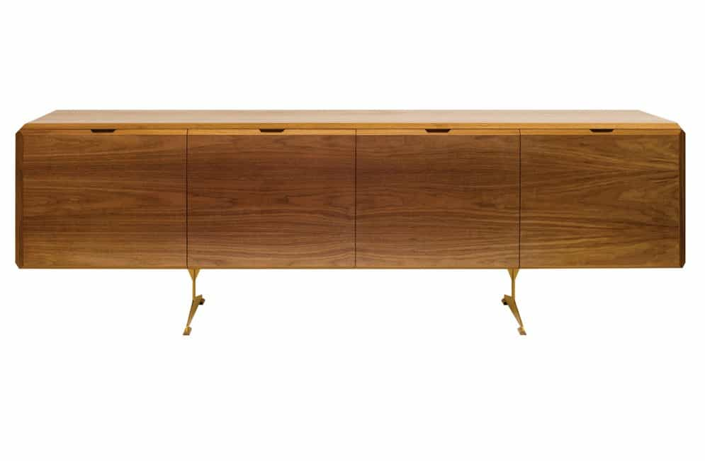 The credenza in Scruton's Emerald Collection is a large piece—96 inches across—but doesn't feel heavy, thanks to chamfered edges and the fine metal legs it rests on. It's designed to tuck away household items—or a bar—without feeling like a