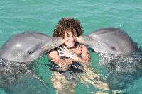 woman kissing by two dolphins in a turquoise water