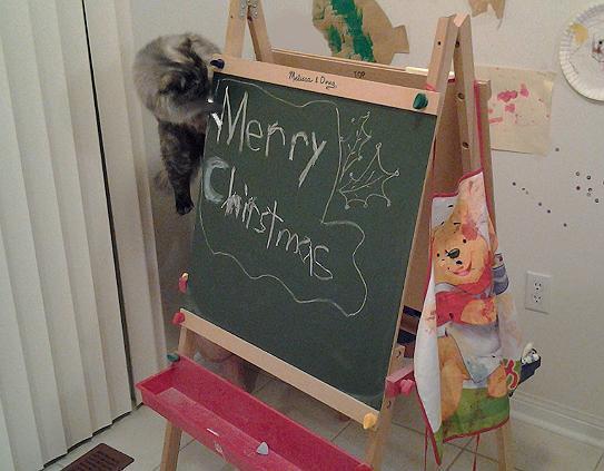Kady draws Merry Christmas on Chalkboard