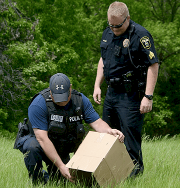 Sgt.Scott Hedrick (left) and Jeff Rukstad (right) of the Columbia Police Department release 13 ducklings