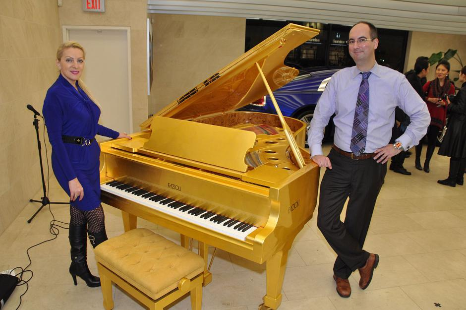 Yana Levkovich, Showcase Pianos Broadway store manager, and Manuel Bernaschek, Showcase Pianos president, pose by the gold-leafed Fazioli piano valued at $535,000.