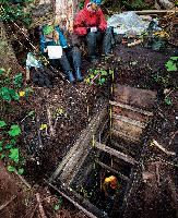 A Hakai archaeologist excavates a six-metre-deep site near the Calvert station while students take notes