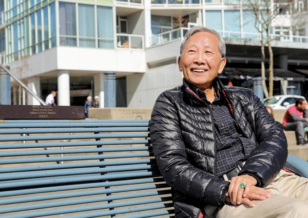 Vancouver Foundation fund holder Monty Jang rests on the Vancouver Seawall park bench that he donated
